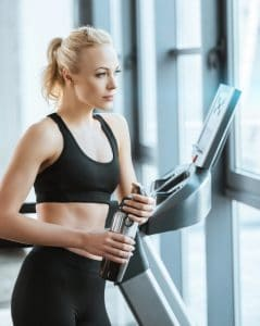 woman resting after workout on treadmill