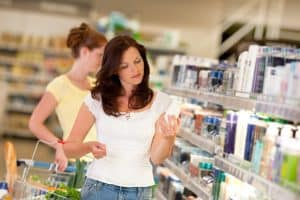 woman checking the active ingredients on the label