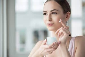 woman in the act of applying cream on her face